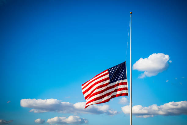 Bright red Stars and Stripes with Perfect American Flag lowered to Half-Mast stars and stripes stock photo