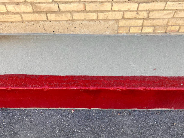 bright red strip painted on sidewalk showing pavement and edge of brick warehouse building stock photo