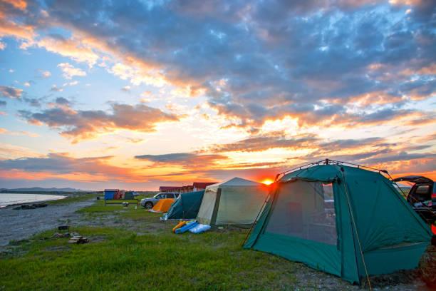 leuchtend roten Sonnenuntergang über den Strand gibt es eine Reihe von Zelten. Touristenlager – Foto