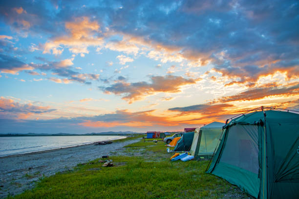 bright red sunset over the beach, there are a number of tents. tourist camp stock photo