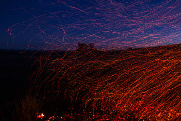 A bright red trail of red sparks flows across the night sky stock photo