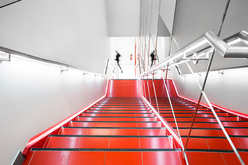 Bright red, white and chrome fire escape with ghosting figure.