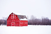 Bright red barn with white trim in white winter landscape and bare trees in the background