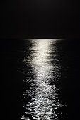Bright reflection of the moon to the very horizon on calm sea waves on a dark night. In black and white