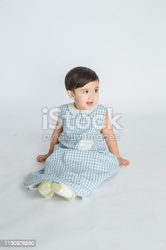 489225417istockphoto bright room. happy boy playing on the floor. A boy in a white t-shirt 1130926850
