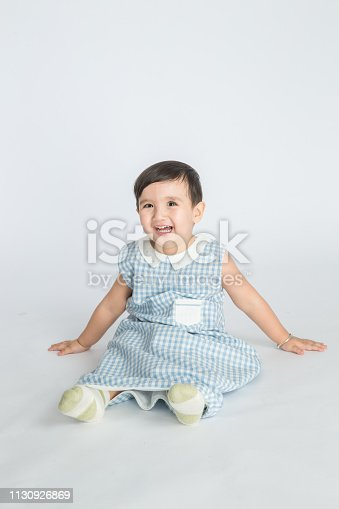 489225417istockphoto bright room. happy boy playing on the floor. A boy in a white t-shirt 1130926869