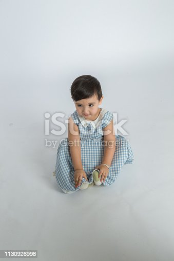 489225417istockphoto bright room. happy boy playing on the floor. A boy in a white t-shirt 1130926998