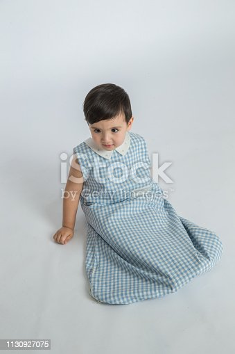 489225417istockphoto bright room. happy boy playing on the floor. A boy in a white t-shirt 1130927075