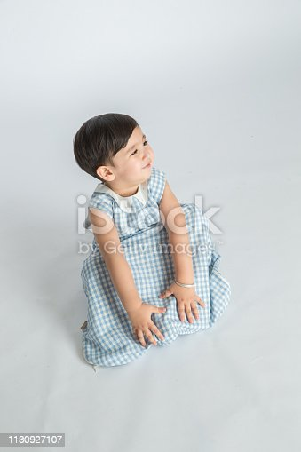 489225417istockphoto bright room. happy boy playing on the floor. A boy in a white t-shirt 1130927107