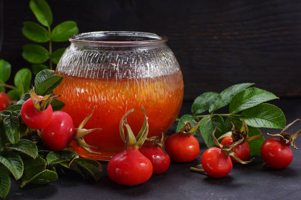 Bright rosehip jam in a jar on the background of leaves and wild rose berries Bright rosehip jam in a jar on the background of leaves and wild rose berries wild rose stock pictures, royalty-free photos & images