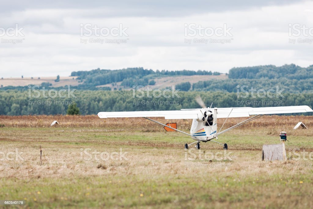 Bright scenic landscape with small propeller plane takes off at the grass. There are trees on background. Selective focus on airplane. Borderless travel concept stock photo