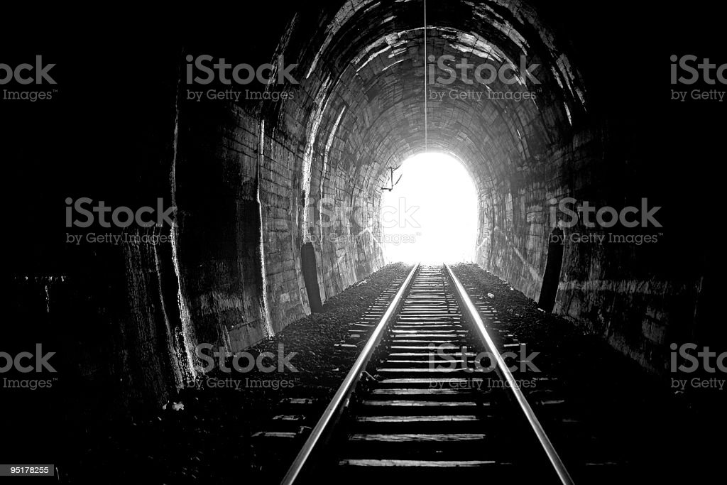 Bright shining light at the end of a dark tunnel stock photo