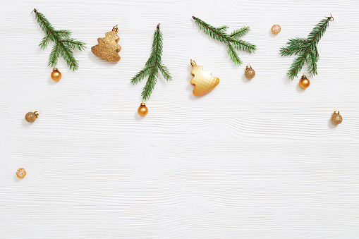 Bright shiny little Christmas balls gold colored with natural green fir tree branches, New Year decoration