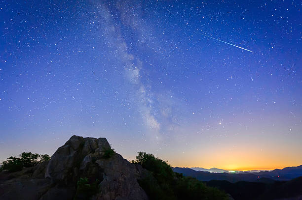 bright shooting star with milky way - shooting stars stock photos and pictures