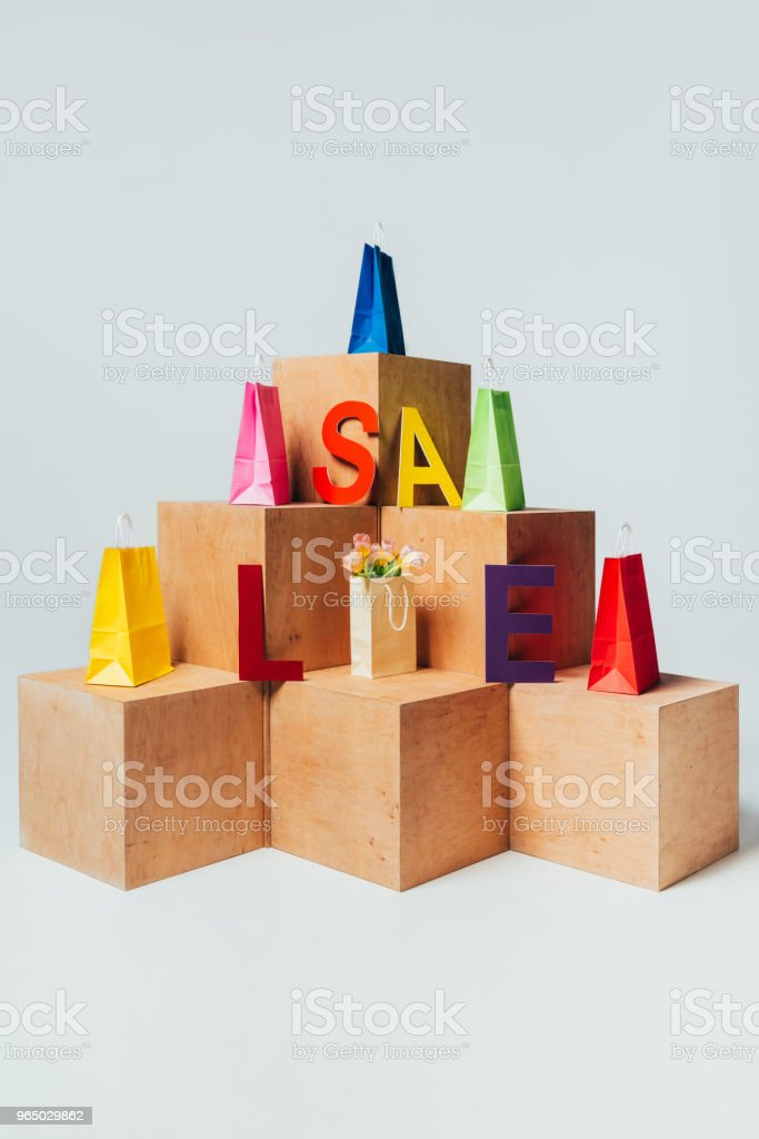 bright shopping bags on wooden stands with sale sign, summer sale concept royalty-free stock photo