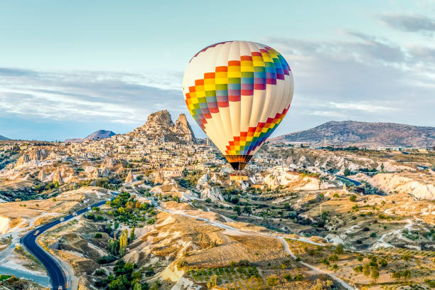 Bright single hot air balloon drifts across highways and dwarfing old town stock photo