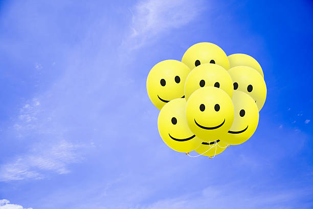 bright smile balloons flying in the blue sky - smiley face stock photos and pictures