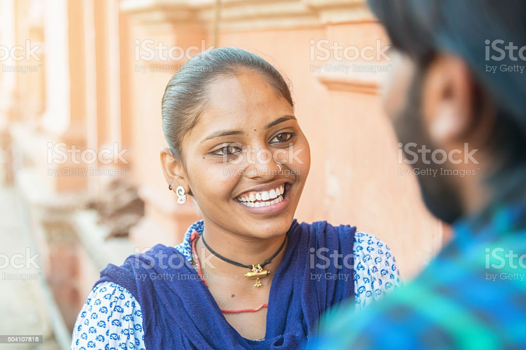 Bright smiling indian young woman talking with her boyfriend stock photo