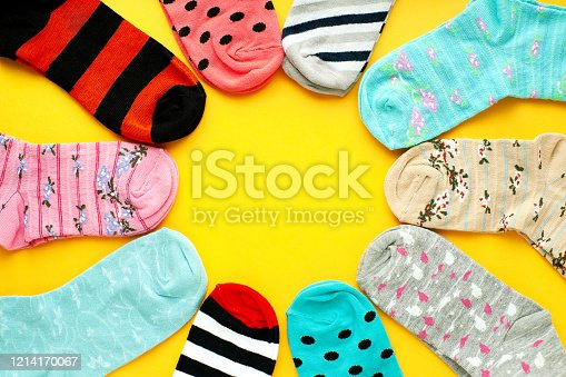 Socks folded in the form of the sun on a yellow background. Socks of different sizes and colors for the cold seasons. Warm clothing.