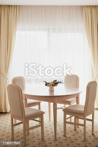Bright spacious dining room with wooden  table, four chairs and big window