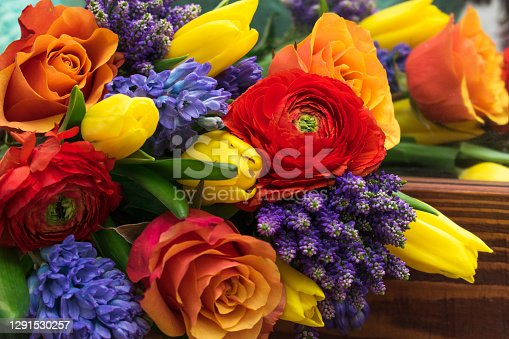 Bright spring bouquet of yellow tulips,blue hyacinths,speedwell,red ranunculus and orange roses lying on the brown wooden table.Present concept for Birthday, mother's Day, 8 March.Selective focus