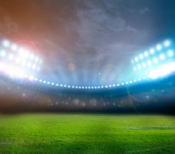 Bright stadium lights illuminating field at night​​​ foto