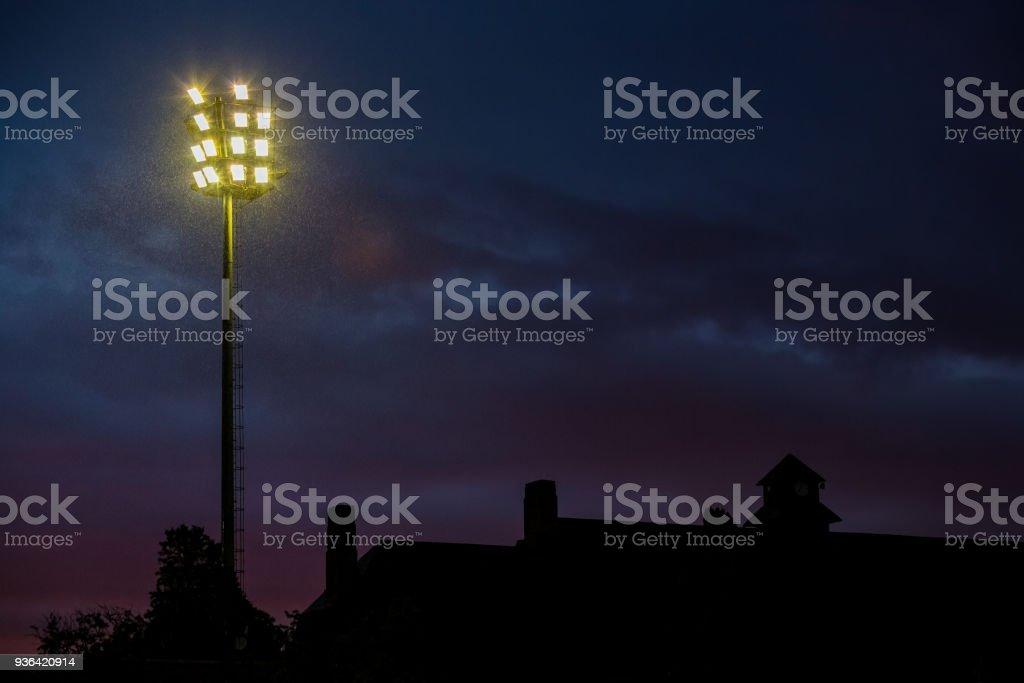 Bright stadium lights on a stormy evening stock photo