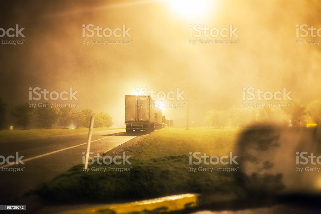 Hazy, dense fog night time image in an expressway rest stop. Several...