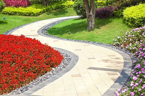 Bright summer garden planted alongside winding tile walkway Beautiful summer garden with a walkway winding its way through elevated walkway stock pictures, royalty-free photos & images