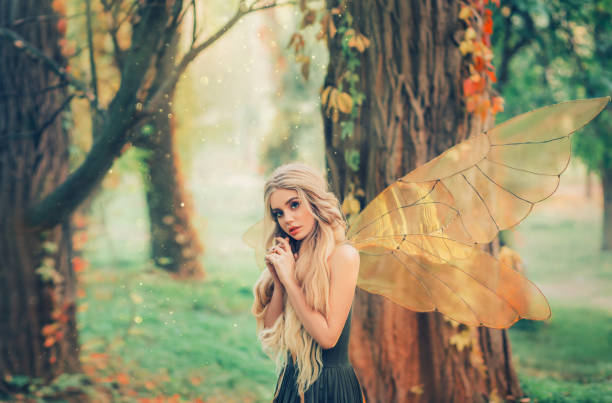 helles sommerfoto mit leuchtenden sonnenstrahlen, geheimnisvolle waldmärchen verliebte sich in prinz, mädchen mit puppengesicht, blond langen haaren und blauen augen, dame in grünem kleid peeps bescheiden, mit interesse - elfenkostüm damen stock-fotos und bilder