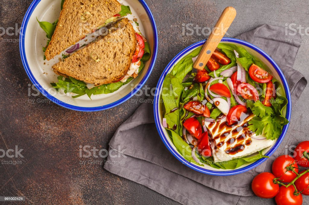 Bright summer salad with tomatoes, onions, balsamic and goat cheese with meat and cheese sandwiches, top view. stock photo