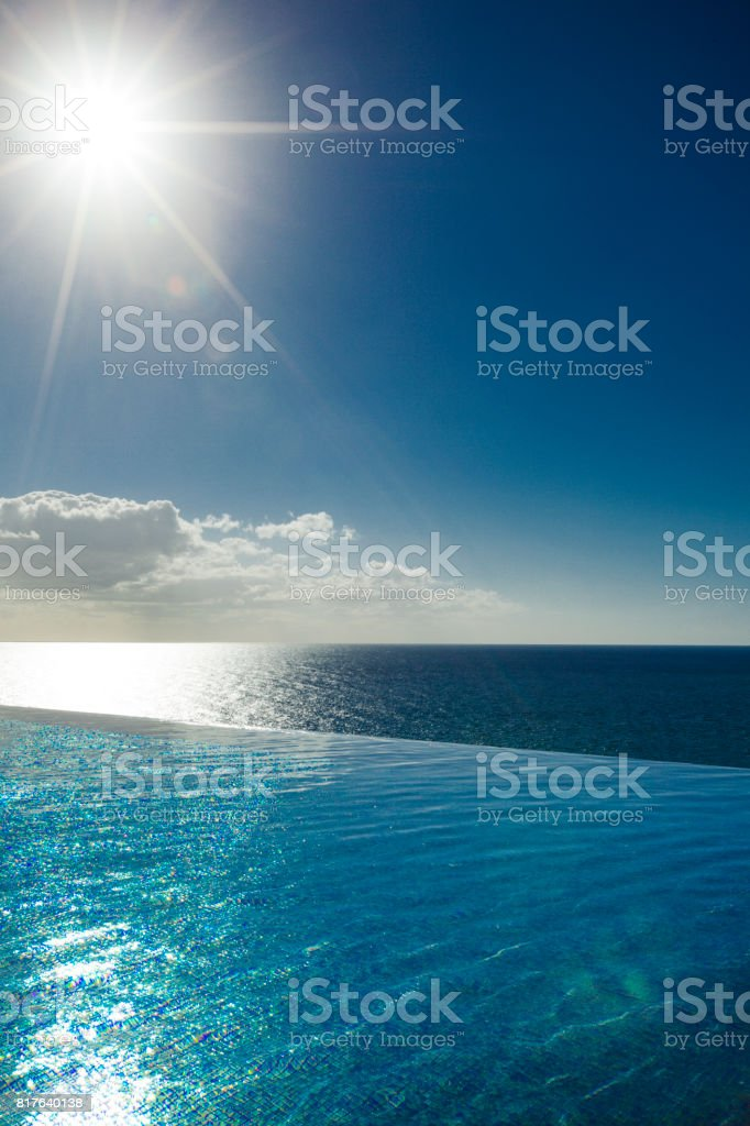 sun reflecting water shapes, infinity swimming pool and horizon over...