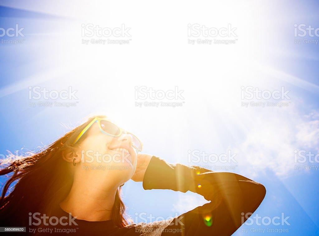 Bright sun dazzles pretty brunette in sunglasses stock photo