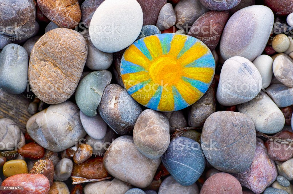 Bright sun painted on pebble. Pebbles background. stock photo