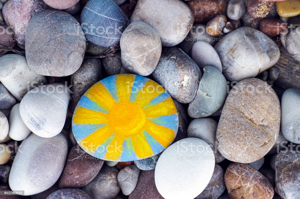 Bright sun painted on pebble with stones background stock photo