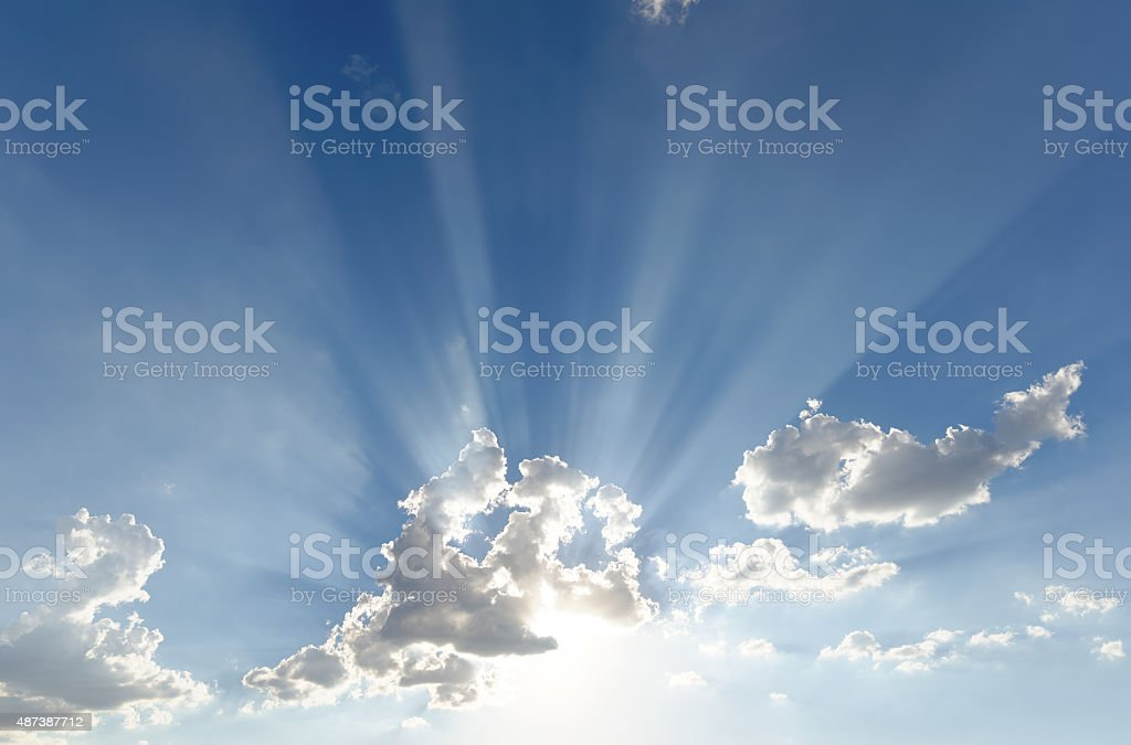 Bright sun rays shooting out of small clouds (wide version) stock photo