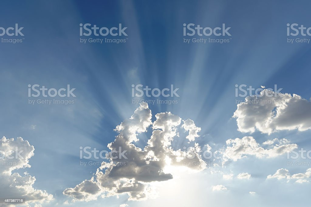 Bright sun rays shooting out of small clouds stock photo