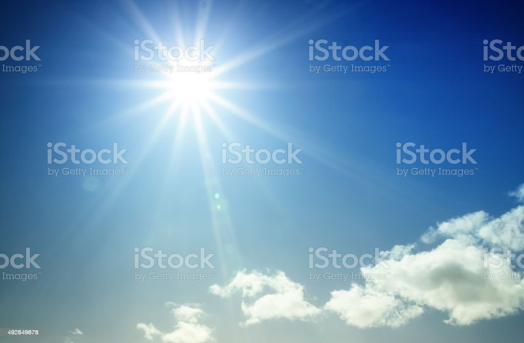Bright sun shining in blue sky with starburst effect stock photo