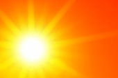 Bright sun with beautiful beams in an orange sky. Space for copy.