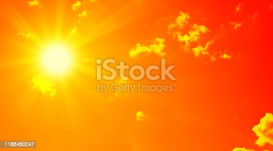 Bright sun with beautiful beams in the sky with clouds. Toned in red color, space for copy.