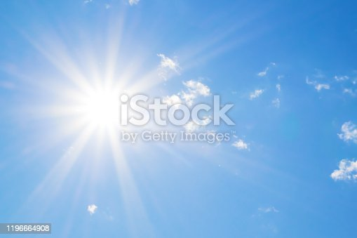 Bright sun with beautiful beams in the blue sky with clouds. Space for copy.