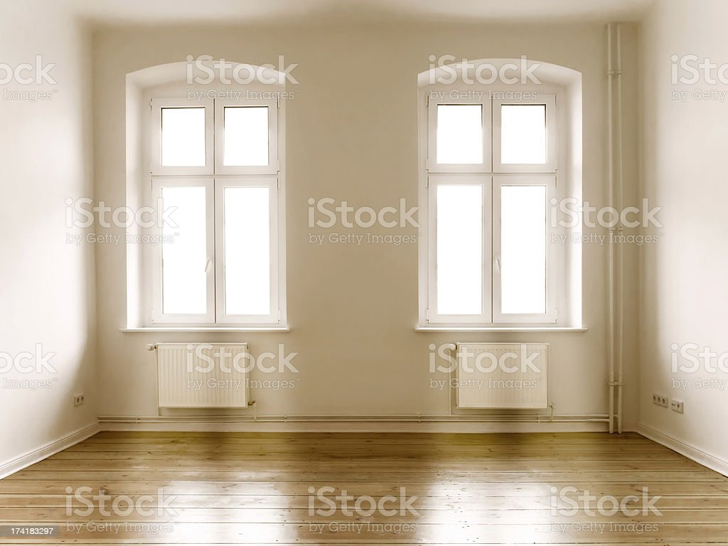 Bright sunlight coming through two windows in empty room royalty-free stock photo