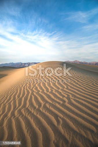Beautiful landscape of sunlight on sand dune of Death Valley National Park. Blue bright sky. Design backgrounds.