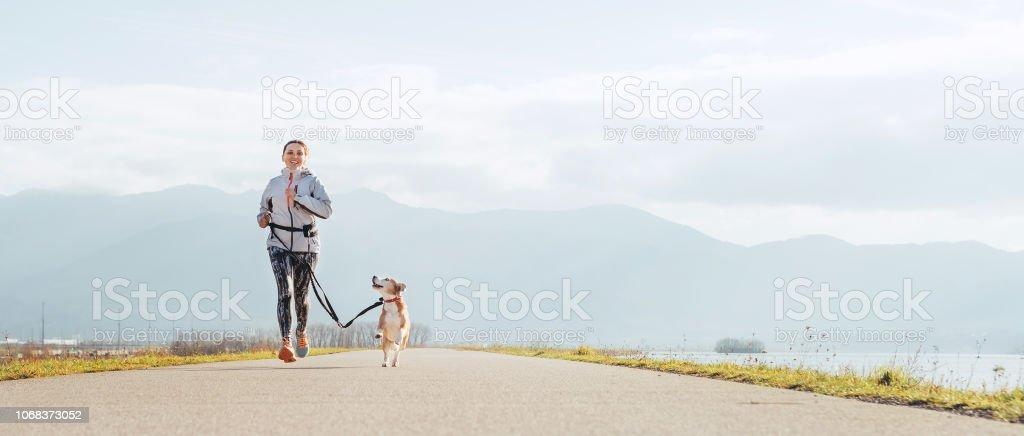 Helle sonnige Morgen Canicross ausübt. Frau läuft mit seiner Beagle Hund und glücklich lächelnd. – Foto