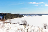 Bright sunny winter day on the shore of a frozen lake