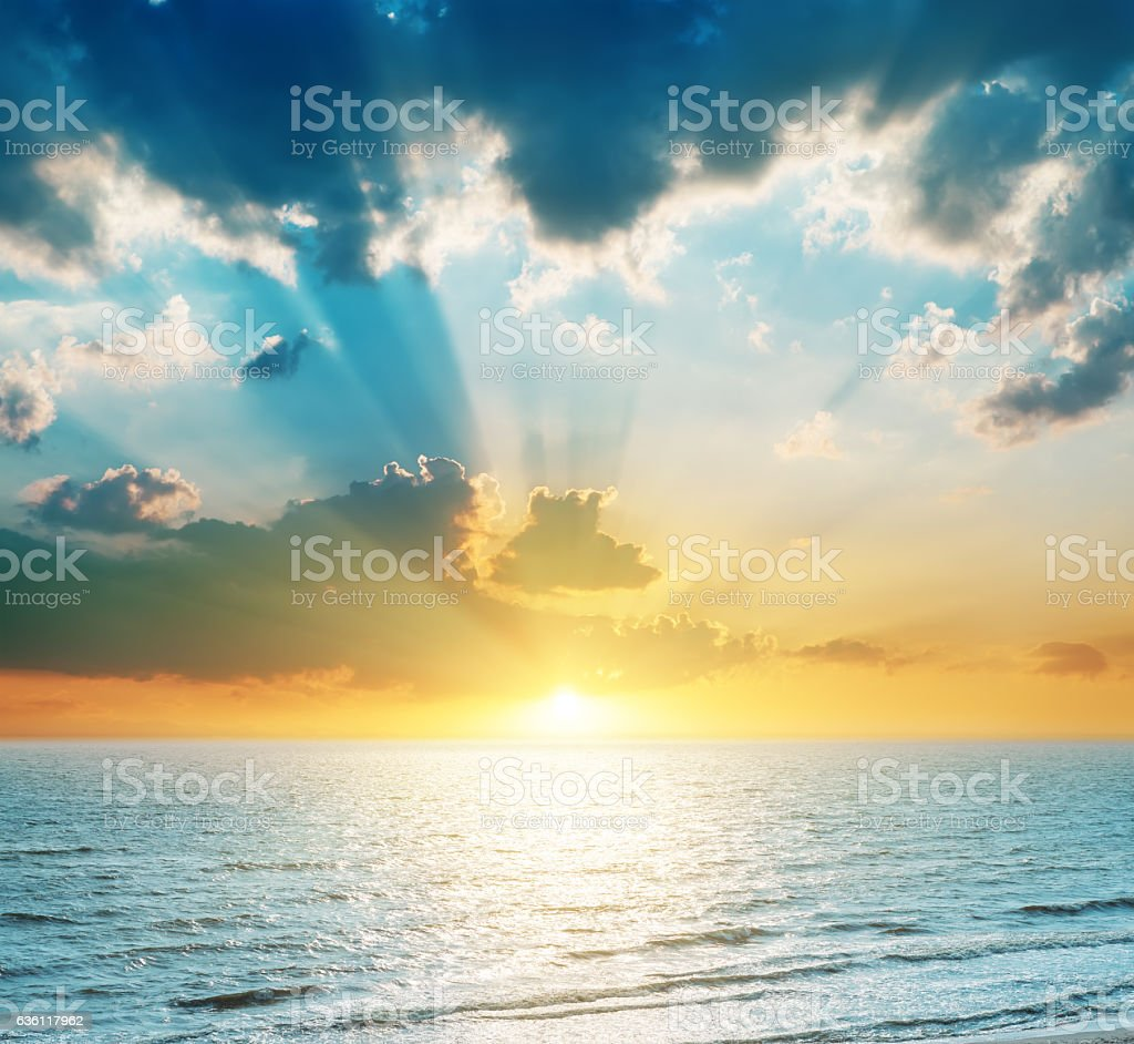 bright sunset in clouds over blue sea - Photo