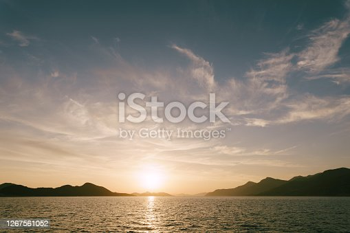A bright sunset in the sea above the mountains. High quality photo