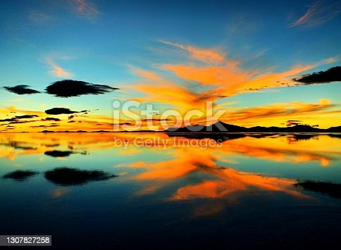 istock Bright sunset on sea. Fantastic fiery orange sky clouds over dark mountains. Golden afterglow at night. Surreal incredible landscape of mysterious lake. Magical heaven reflection in water. 1307827258