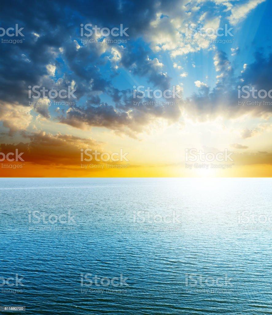 bright sunset over blue sea stock photo