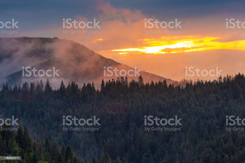Bright sunset over foggy mountains. Vivid sun through the clouds over...